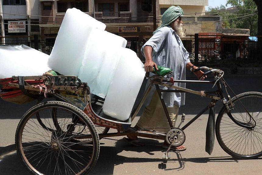 An Indian worker uses a rickshaw to transport ice from an ice factory in Amritsar on May 27, 2015. -- PHOTO: AFP