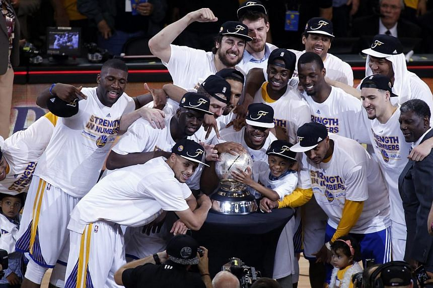 The Golden State Warriors pose for a photograph with the NBA Western Conference Finals trophy after defeating the Houston Rockets in Game five of the NBA Western Conference Finals at Oracle Arena in Oakland, California, USA, on May 27, 2015. -- PHOTO