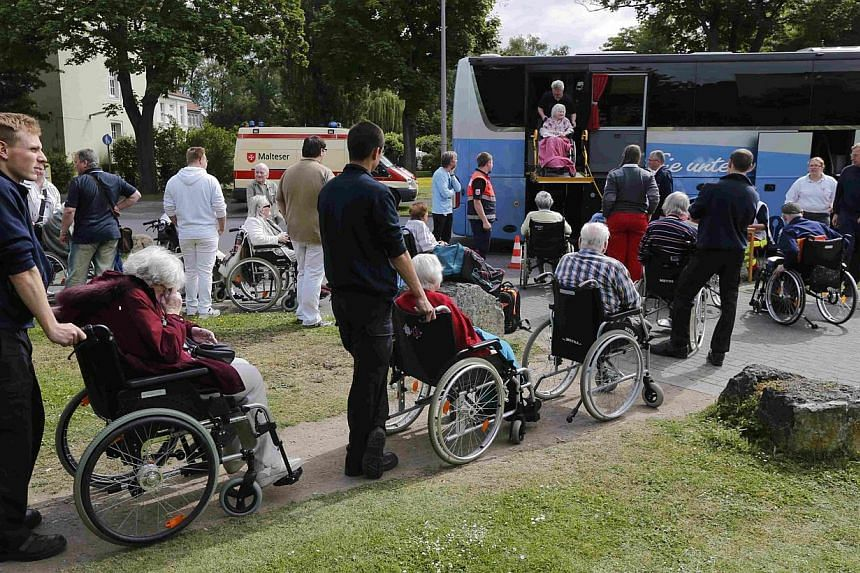 Worker's of Germany's Arbeiter Samariter Bund ASB, a welfare organisation engaged in civil protection, rescue and social services line up handicapped pensioners to evacuated a nearby nursing home in a special bus in Cologne, Germany, on May 27, 2015.