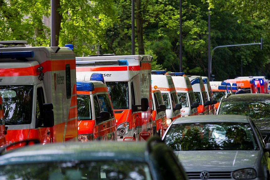 Ambulances wait at a social services facility after a WWII one-tonne bomb was discovered near the Muelheim bridge in Cologne, Germany, on May 27, 2015. -- PHOTO: EPA