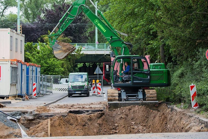 A excavator at work at the location of a WWII one-tonne bomb near the Muelheim bridge in Cologne, Germany, on May 27, 2015. About 20,000 people were forced to leave their homes while the bomb was made safe. -- PHOTO: EPA