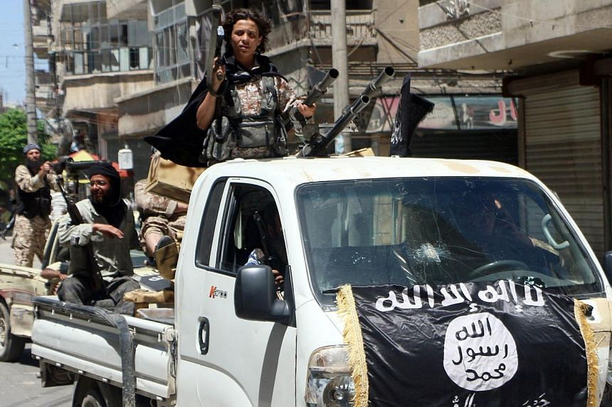 Fighters from Al-Qaeda's Syrian affiliate Al-Nusra Front driving in armed vehicles in the northern Syrian city of Aleppo as they head to a frontline, on May 26, 2015. -- PHOTO: AFP