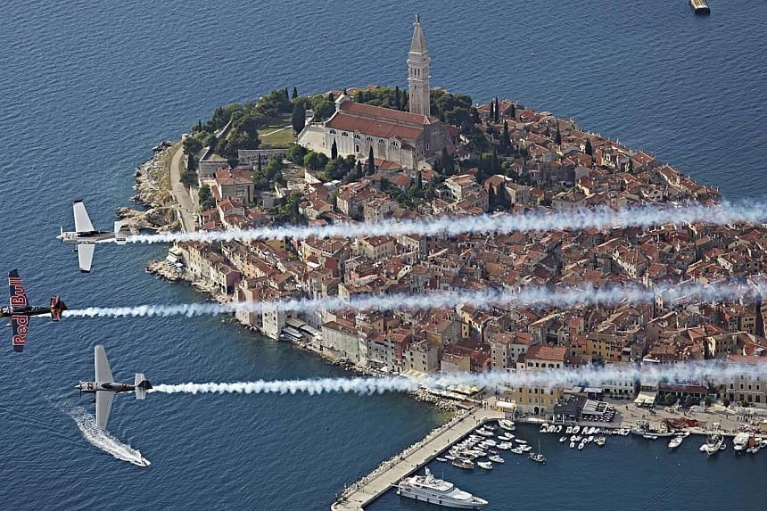 Planes flying in formation over the city of Rovinj during the Red Bull Air Race World Championship in Croatia. -- PHOTO: EPA