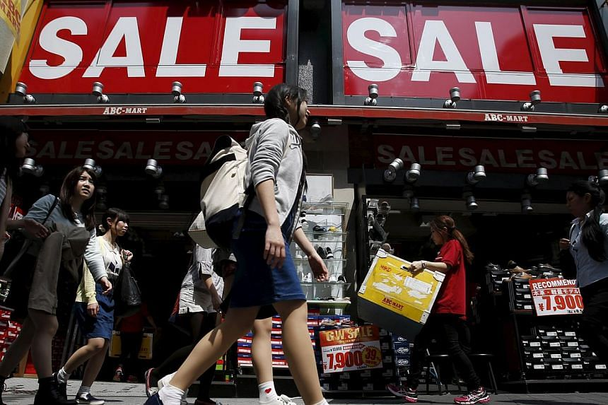 A shop clerk (second, right) carrying a box of shoes under sale signboards at a shoes retail store at a shopping district in Tokyo, Japan, on April 28, 2015. -- PHOTO: REUTERS