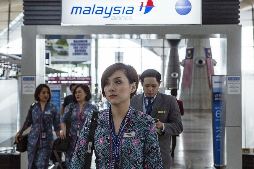 Malaysian Airline System Bhd. (MAS) air crew walk through Kuala Lumpur International Airport (KLIA) in Sepang, Malaysia, on Aug 26, 2014. -- PHOTO: BLOOMBERG