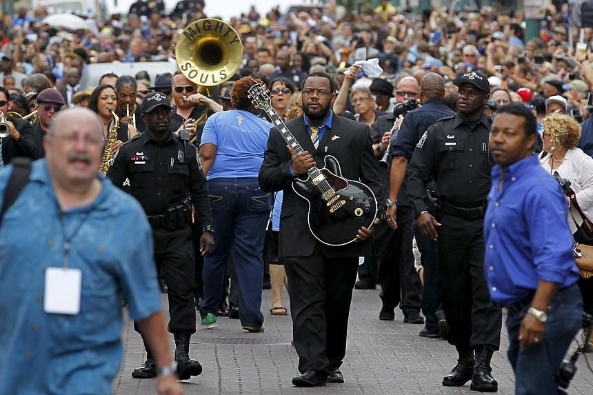 """Rodd Bland, son of Bobby """"Blue"""" Bland, carrying the iconic Gibson guitar named """"Lucille"""" belonging to the late B.B. King during a procession down Beale Street in Memphis, Tennessee on May 27, 2015. -- PHOTO: REUTERS"""