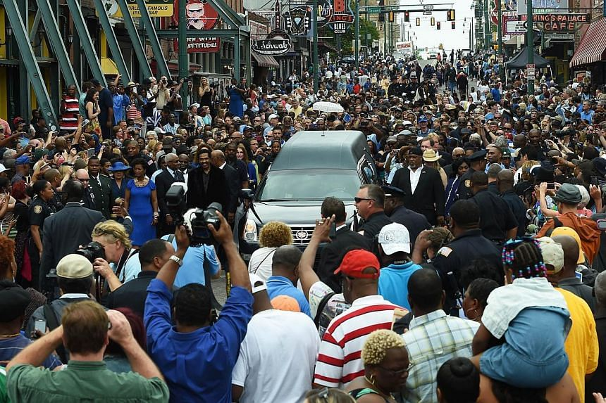 A hearse carrying the remains of blues musician B.B. King drives on Beale Street during a processional on May 27, 2015 in Memphis, Tennessee. -- PHOTO: AFP