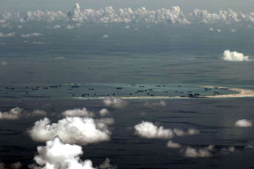 An aerial file photograph taken though a glass window of a Philippine military plane shows the alleged on-going land reclamation by China on mischief reef in the Spratly Islands in the South China Sea, west of Palawan, Philippines, on May 11, 2015. -