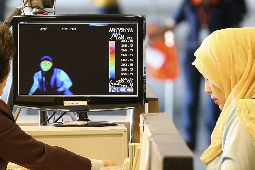 Passengers from the Middle East passing by a thermal camera at Incheon airport, west of Seoul, South Korea, on May 21, 2015. -- PHOTO: EPA