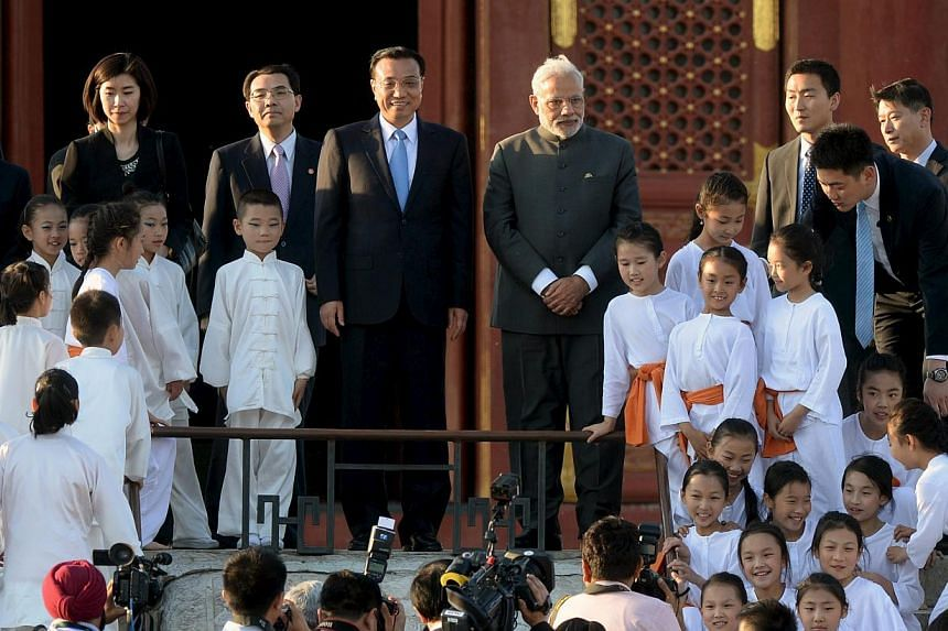 Indian Prime Minister Narendra Modi (centre, right) and Chinese Premier Li Keqiang (centre, left) pose for pictures with child performers of a taiji and yoga event, at the Temple of Heaven park in Beijing, China on May 15, 2015. -- PHOTO: AFP
