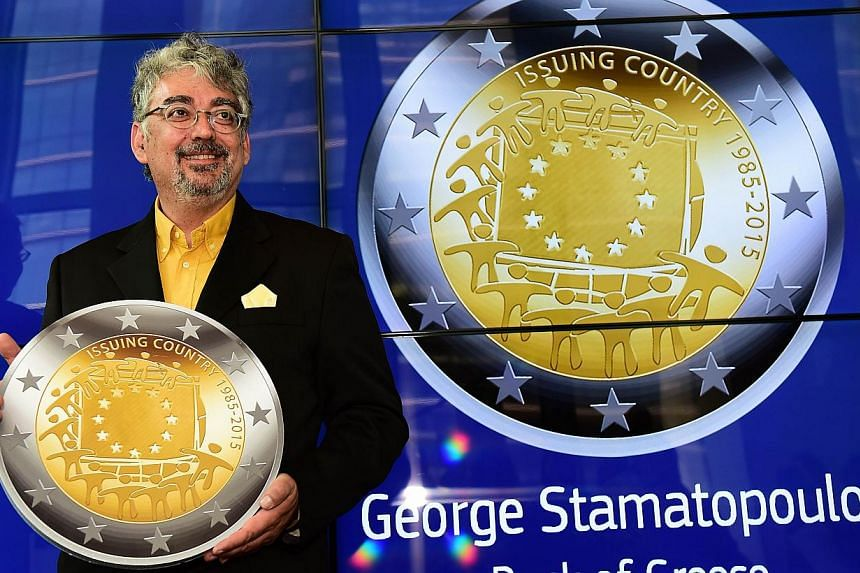 George Stamatopoulos, an engraver of the Bank of Greece, holds a replica of the commemorative two euro coin he designed, during a ceremony announcing that the coin design was chosen to mark the 30th anniversary of the adoption of the European flag as