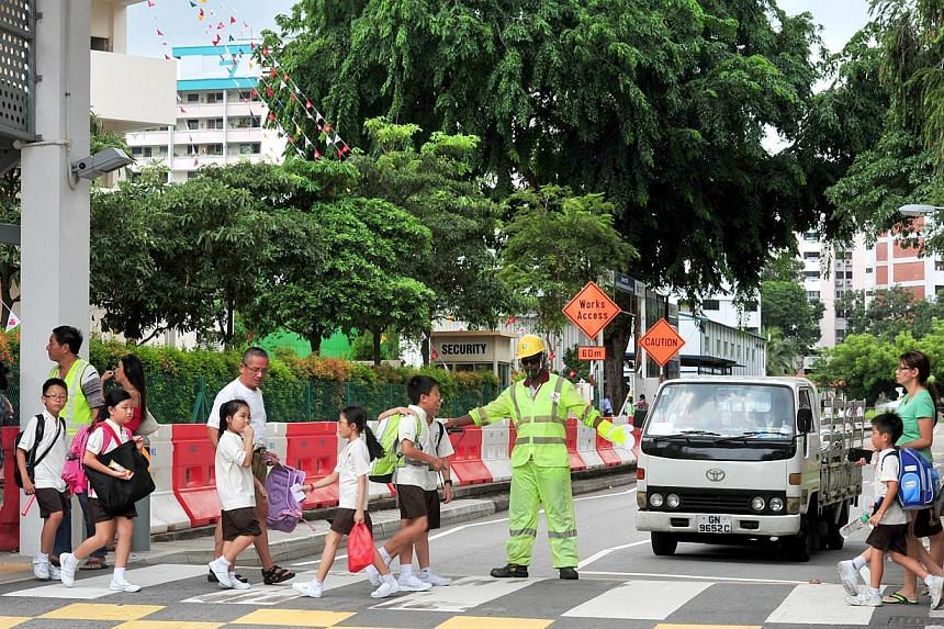 A traffic marshal guiding pupils from Hong Wen School across a zebra crossing. Sweden and the UK topped a survey of 32 countries in terms of road safety, and while Singapore was not included in the survey, data shows that it would have ranked close t