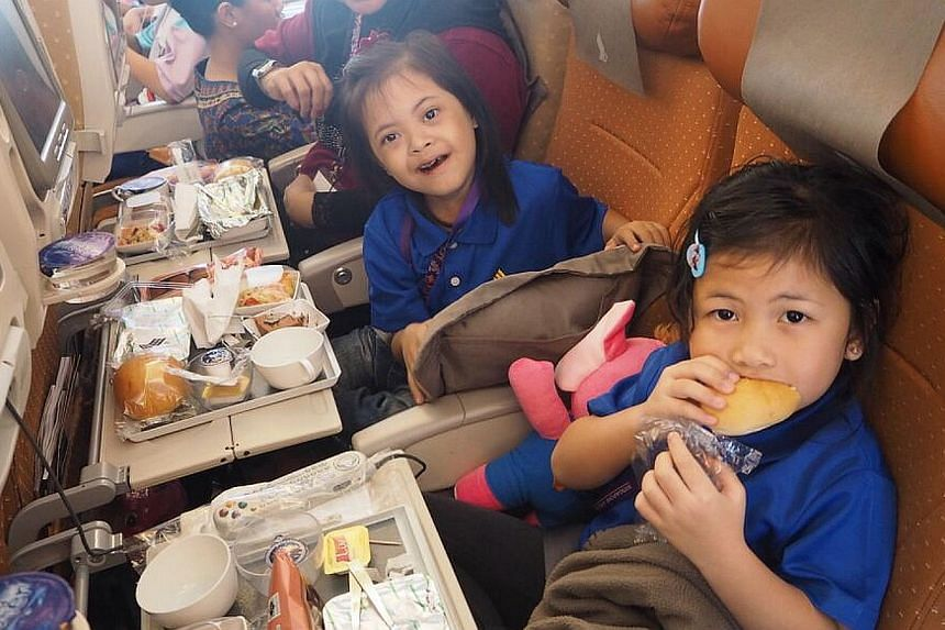 Beneficiaries enjoying their meals during the flight. -- PHOTO: SINGAPORE AIRLINES