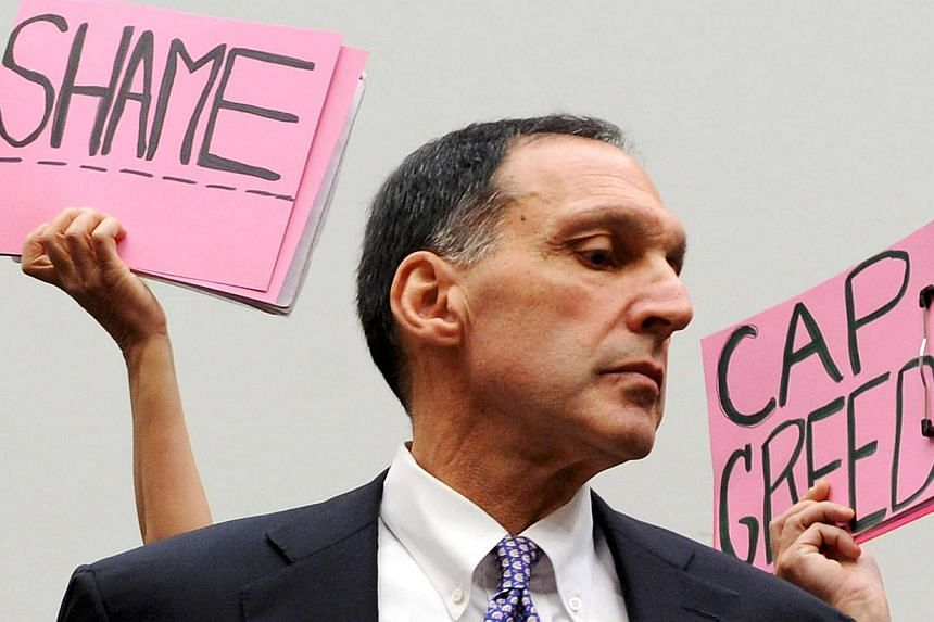 Protestors holding signs behind Richard Fuld as he takes his seat to testify at a House Oversight and Government Reform Committee hearing on the causes and effects of the Lehman Brothers bankruptcy, on Capitol Hill in Washington in this Oct 6, 2008 f