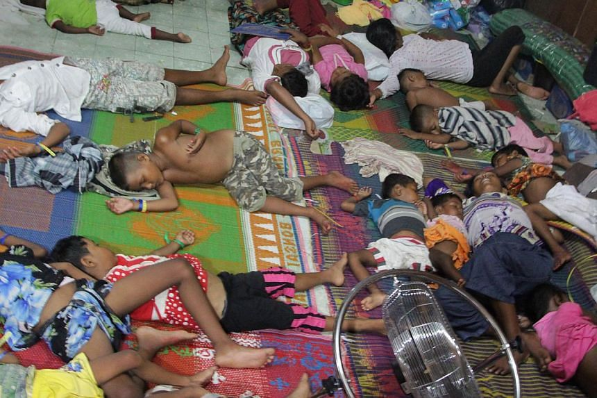 Rohingya children and women from Myanmar sleep in a confinement area in Bayeun, located in Indonesia's Aceh province after a boatload of Rohingya migrants from Myanmar and Bangladesh were rescued by Indonesian fishermen on May 20 off the Aceh coast.