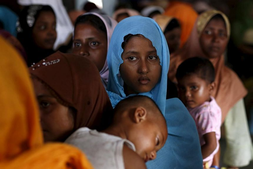 Rohingya migrants who arrived in Indonesia last week by boat wait in line to receive donations at a temporary shelter in Aceh Timur regency, near Langsa in Indonesia's Aceh Province on May 25, 2015. -- PHOTO: REUTERS