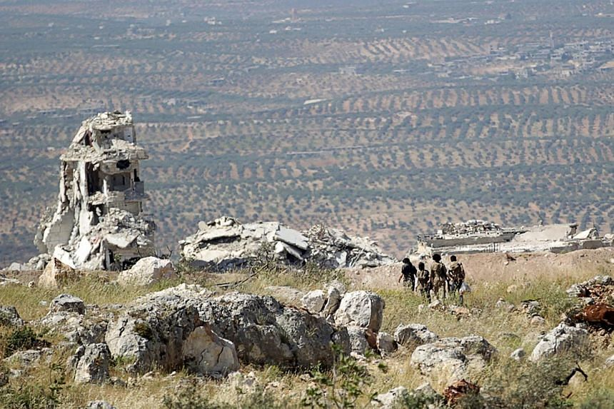 Rebel fighters from the Ahrar al-Sham Islamic Movement walking on a hill in Jabal al-Arbaeen, which overlooks the northern town of Ariha. -- PHOTO: REUTERS