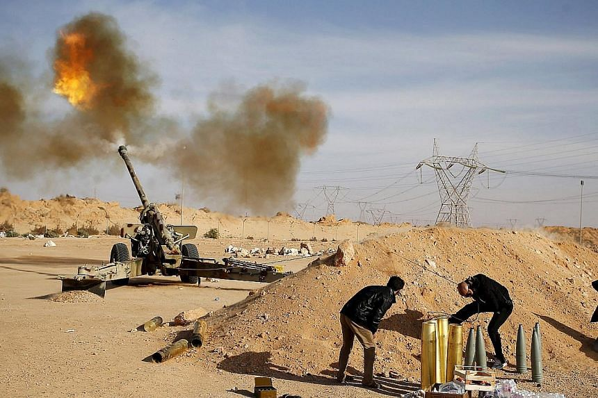 Libya Dawn fighters fire an artillery cannon at IS militants near Sirte on March 19, 2015. ISIS has seized control of the airport in the city of Sirte after forces of a Tripoli-based Libyan government withdrew, a spokesman said on Friday. -- PHOTO: R
