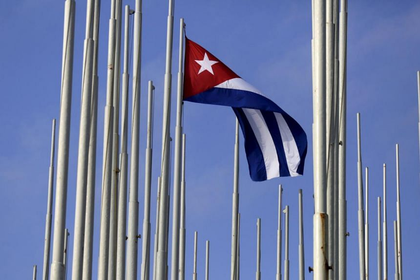The Cuban flag flies in front of the US Interests Section (background), in Havana May 22, 2015. -- PHOTO: REUTERS