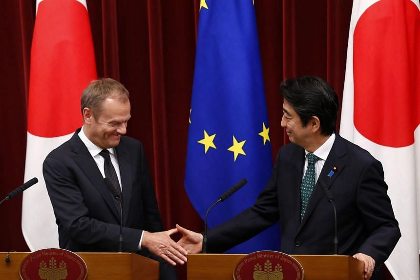 Japan' Prime Minister Shinzo Abe and European Council President Donald Tusk shake hands after a joint news conference after a Japan-EU summit meeting in Tokyo on May 29, 2015. The European Union and Japan are concerned about unilateral actions that c