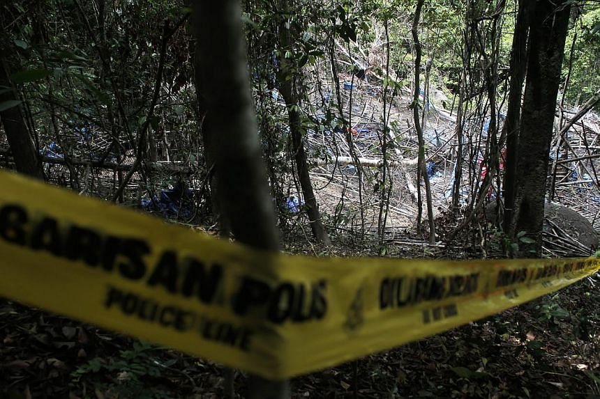 Police tape cordoned off the site of an abandoned camp in which graves were found at Wang Burma hills at Wang Kelian, Perlis, Malaysia, on May 26, 2015. -- PHOTO: EPA