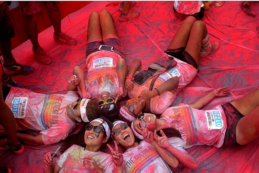 A group of participants lying on the ground after completing The Color Run at Sentosa on Aug 30, 2014. -- PHOTO:THE NEW PAPER FILE