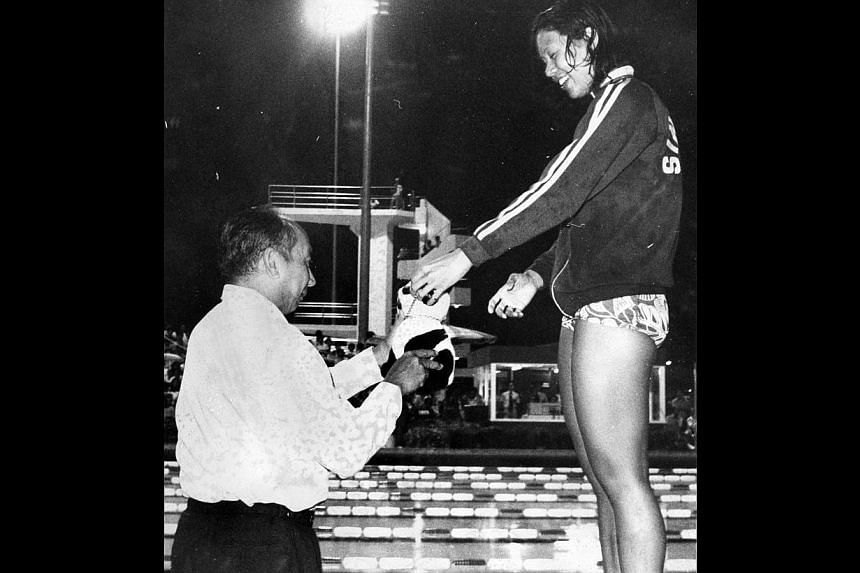 Singapore's original swim queen Pat Chan showing Defence Minister Goh Keng Swee her lucky mascot, a teddy bear, after receiving the 100m backstroke gold medal from him. Heather Merican clearing the last barrier to win the 200m hurdles easily from tea