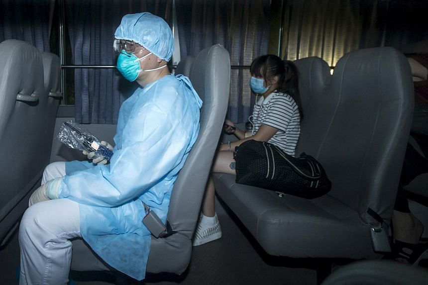 A health worker with protective suits sitting with people (right) who came into close contact with the Korean Mers patient arrive at Lady MacLehose Holiday Village in Sai Kung, where they will spend two weeks in quarantine, in Hong Kong, China on May
