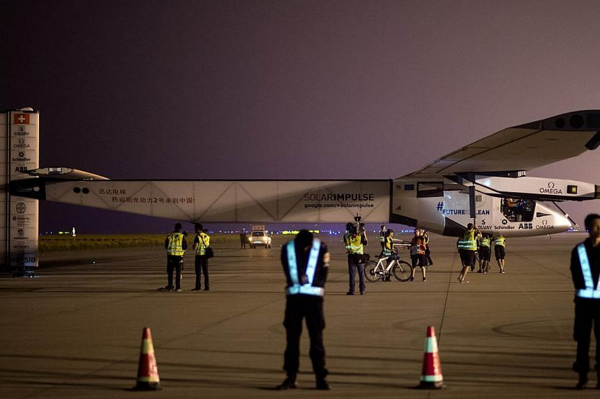 Chinese security staff members standing guard shortly before the Swiss-made solar-powered plane Solar Impluse 2 took off from Nanjing's Lukou International Airport in China's eastern Jiangsu province on May 31, 2015. -- PHOTO: AFP
