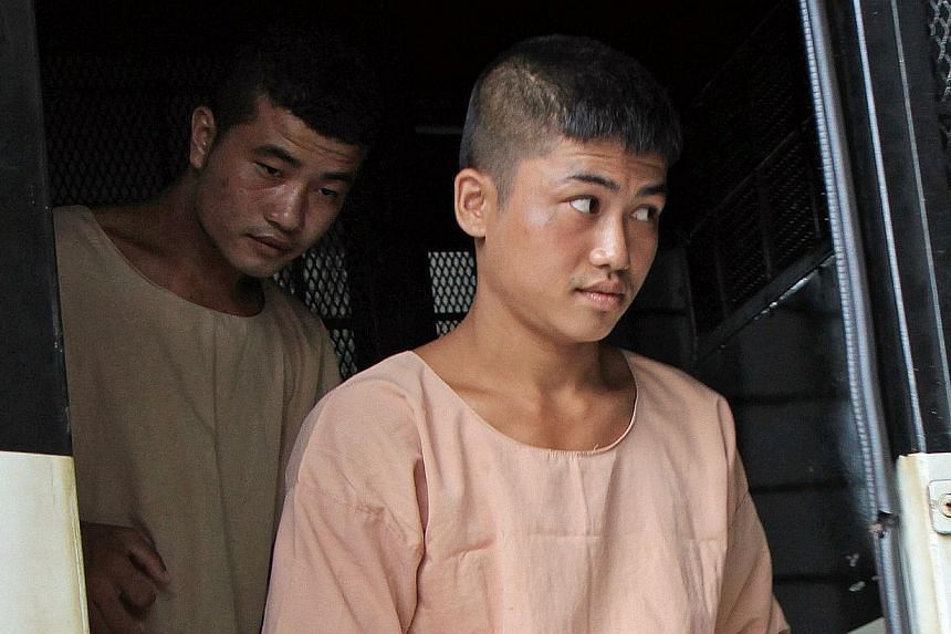 Myanmar defendants, migrant workers Zaw Lin (left) and Win Zaw Tun walk out of a police truck as they arrive for a hearing at a criminal court in Thailand's southern island of Koh Samui on April 30, 2015. -- PHOTO: AFP