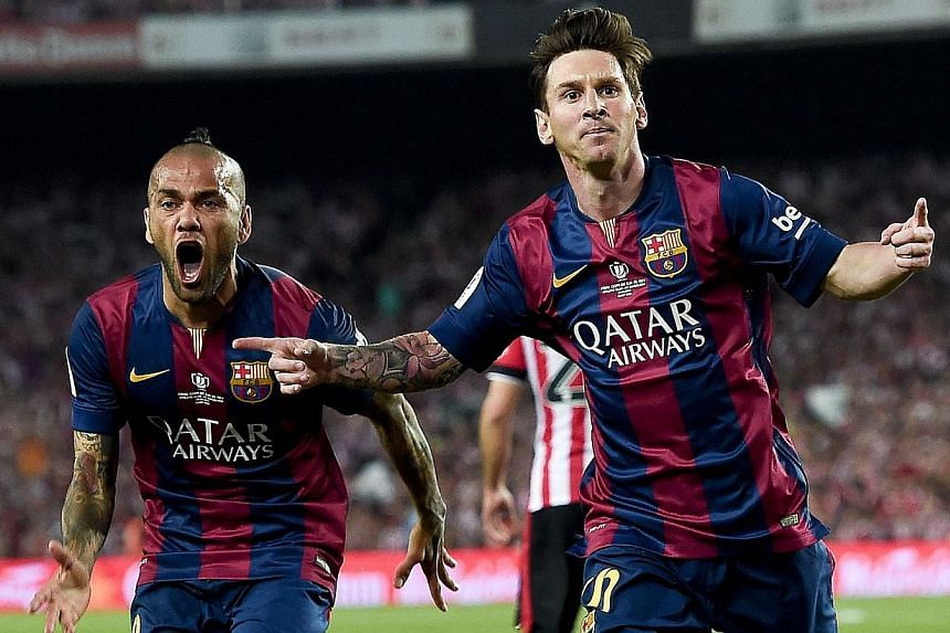 Barcelona's Lionel Messi (right) celebrating a goal along with teammate Dani Alves as the Catalans triumphed 3-1 in the King's Cup final at Camp Nou, Barcelona, on May 30, 2015. -- PHOTO: AFP