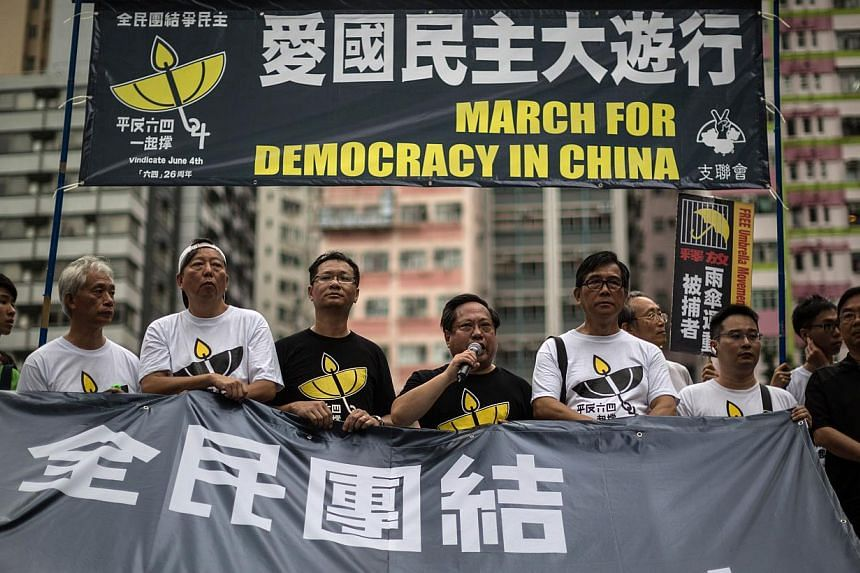 Pro-democracy protesters take turns to speak as they stand behind a huge banner in Hong Kong on May 31, 2015, before a rally to commemorate the 1989 crackdown at Tiananmen Square in Beijing, prior to the incident's 26th anniversary on June 4. Hong Ko