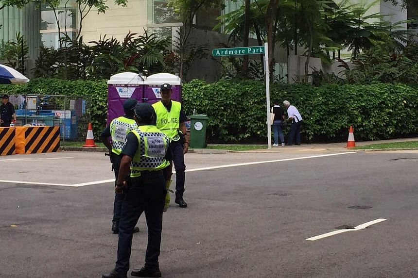 Police officers standing guard at the checkpoint at the junction of Ardmore Park and Anderson Road, where the car was apparently asked to stop for a boot check on Sunday, May 31, 2015. -- ST PHOTO: LEE MIN KOK