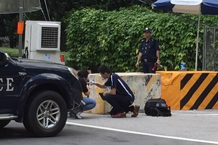 A CID officer checking and taking photos of the barricade at the Ardmore Park checkpoint on Sunday, May 31, 2015. -- ST PHOTO: LEE MIN KOK