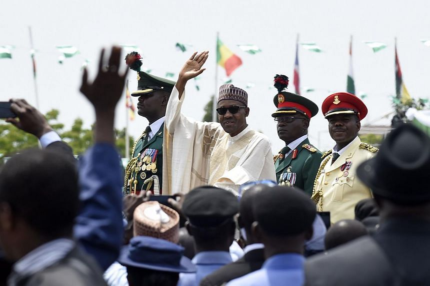 Nigerian President Muhammadu Buhari (centre) waves to the crowd during his inauguration ceremony as President of Nigeria, in Eagle Square in Abuja, Nigeria, on May 29, 2015. -- PHOTO: AFP