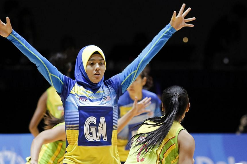Malaysia's Izyan Syazana Mohd Wazir (left) defending against Myanmar's Kyaw Kin Sandar in their SEA Games netball match on Sunday, May 31, 2015. Defending SEA Games champions Malaysia thrashed Myanmar 84-22. -- PHOTO: REUTERS