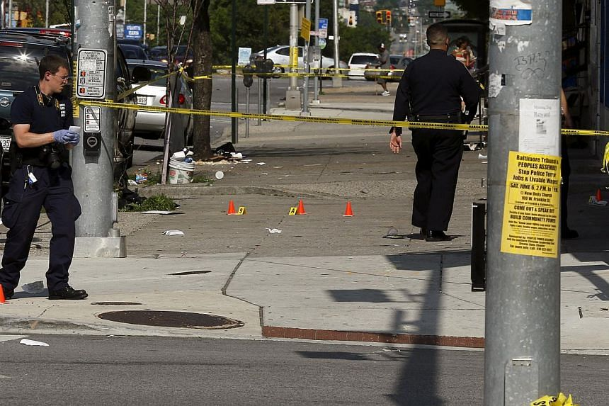 Police place evidence markers at spots where shell casings have been found at the scene of a shooting at the intersection of West North Avenue and Druid Hill Avenue in West Baltimore, Maryland on May 30, 2015. -- PHOTO: REUTERS