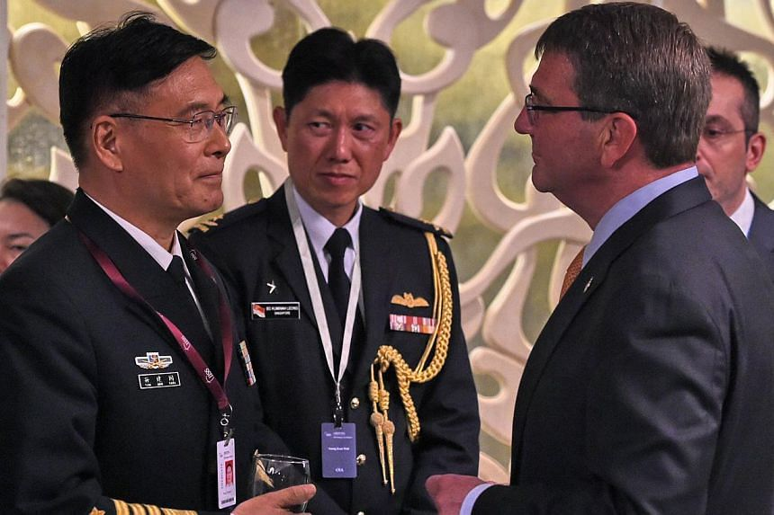 Sun Jianguo (left) from the Chinese People's Liberation Army Navy, chats with US Secretary of Defense Ashton Carter (right) during the ministerial luncheon at the 14th Asia Security Summit, the International Institute for Strategic Studies (IISS) Sha