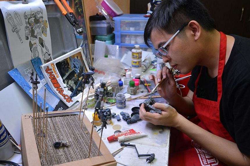 Mr Lin Zhisheng(above), a food and beverage manager who owns more than 250 kits. He is applying a coat of paint to a model, a process which usually takes him about two hours to finish. -- ST PHOTO: BENSON ANG