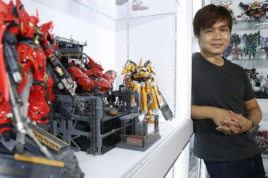 When claims executive Kenny Lim assembles the Gundam models, he imagines himself as a pilot controlling a massive robot and taking down foes. He is among the few people here who own more than 500 Gundam kits. -- ST PHOTO: KEVIN LIM
