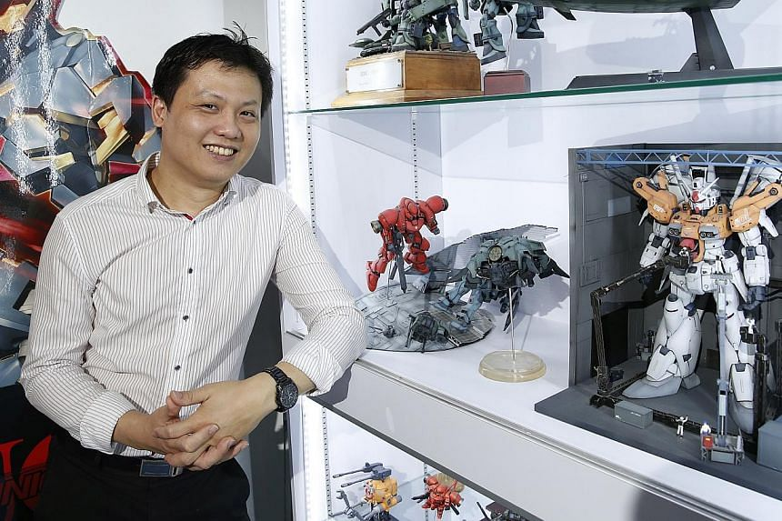 Building manager Leon Ku owns more than 500 Gundam kits and says he is drawn to the challenge of making realistic Gundam models through detailed painting and weathering effects. -- ST PHOTO: KEVIN LIM