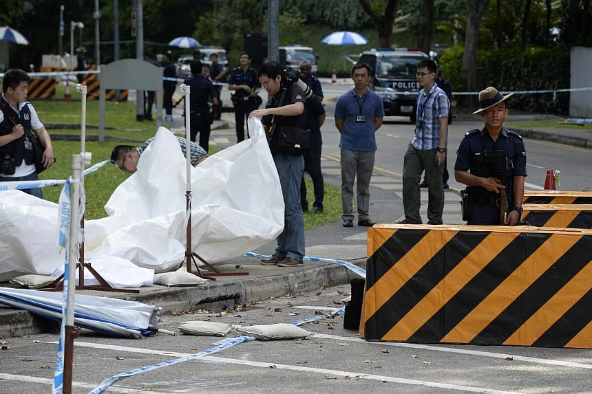 Police officers at Orange Grove Road.Three men travelling in a car dashed through a checkpoint and police barricades near Shangri-La Hotel when police asked to inspect the car boot on Sunday, May 31, 2015.Police fired at the car, and one