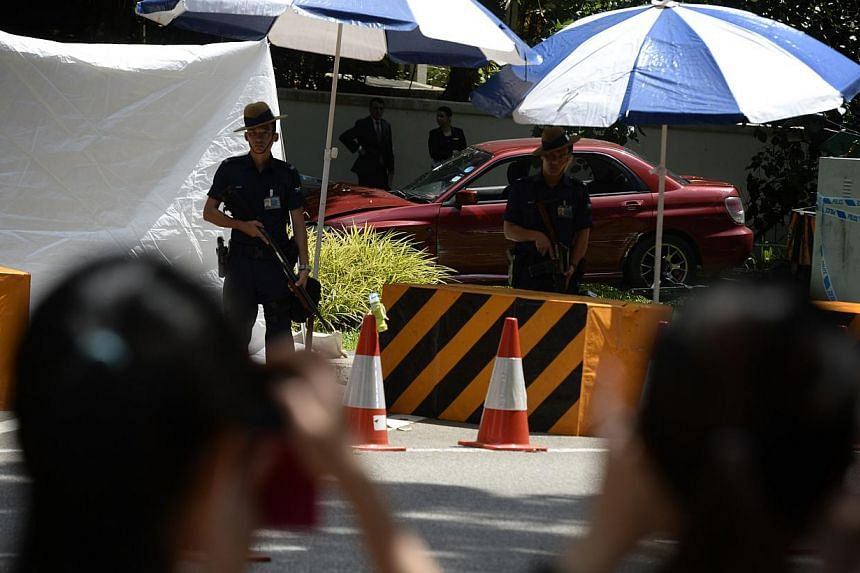 Gurkhas standing guard around the red car driven by the man who was shot dead. Police shot at the vehicleon Sunday, May 31, 2015..-- ST PHOTO: MARK CHEONG