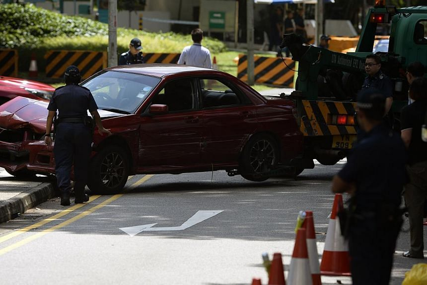 The red car which police shot atbeing towed away on Sunday, May 31, 2015. -- ST PHOTO: MARK CHEONG