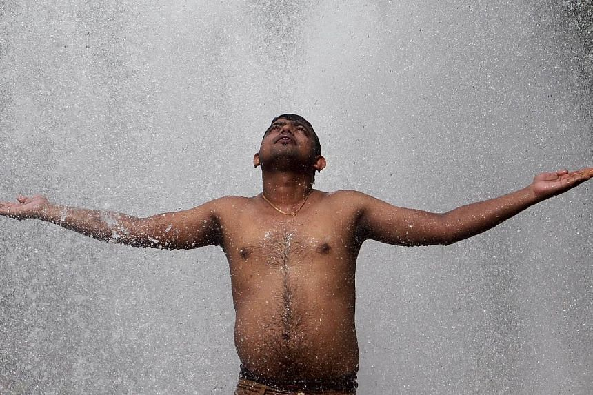 A man cools himself off at a municipal corporation water treatment plant on a hot summer day in Agartala, India, on May 31, 2015.Scattered rain on Sunday brought much-needed but only temporary relief to parts of India hit by a long heatwave as