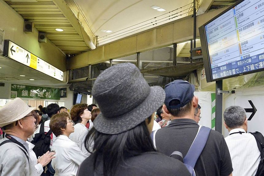 Passengers check train schedules after train services were suspended following an earthquake at Shinbashi station in Tokyo, in this photo taken by Kyodo on May 30, 2015.Seismologists on Sunday, May 31, warned Japan to stay vigilant for the next