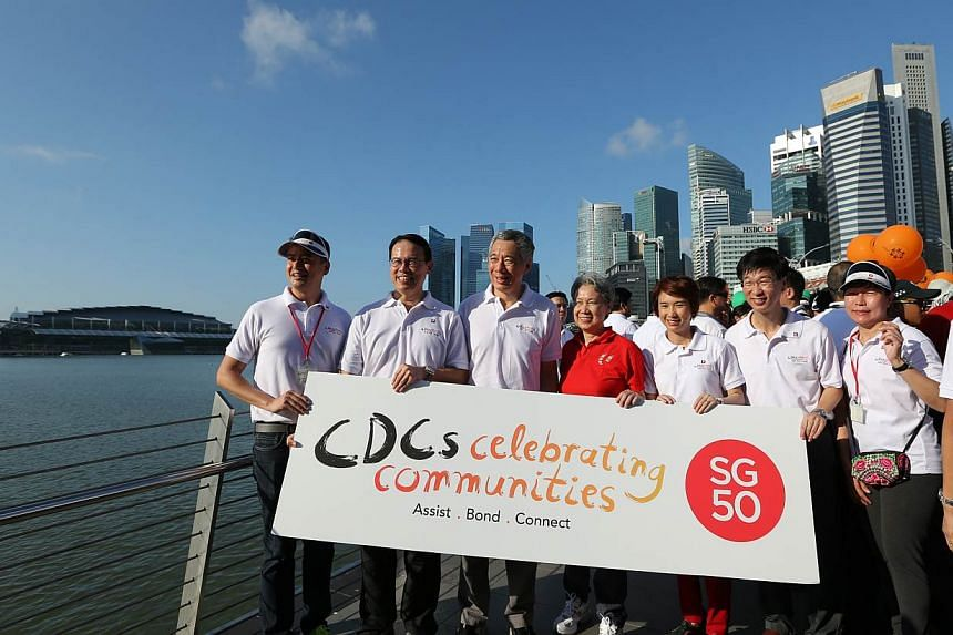 PM Lee Hsien Loong posing with a banner at the CDCs' Celebrating Communities' event, a 2.5km community parade and brisk walk. -- ST PHOTO: ONG WEE JIN