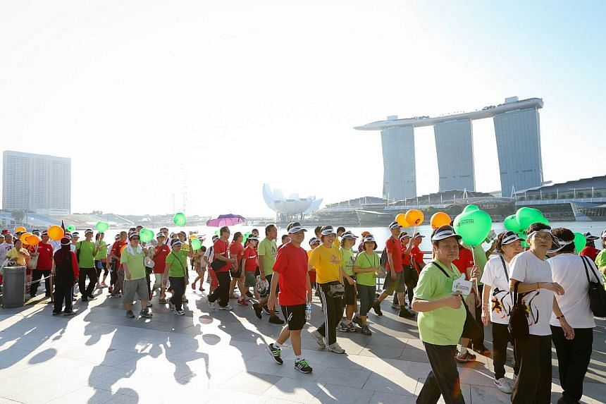 Members of the public walking around the Marina Bay area during the CDCs' Celebrating Communities' event, a 2.5km community parade and brisk walk.-- ST PHOTO:ONG WEE JIN