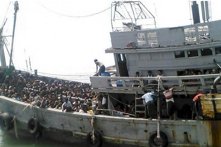 A handout picture released by the Myanmar Ministry of Information on May 30, 2015 shows migrants who were seized by the Myanmar navy in a boat near the Irrawaddy delta in Myanmar, on May 29, 2015.Myanmar's navy briefly detained and turned back