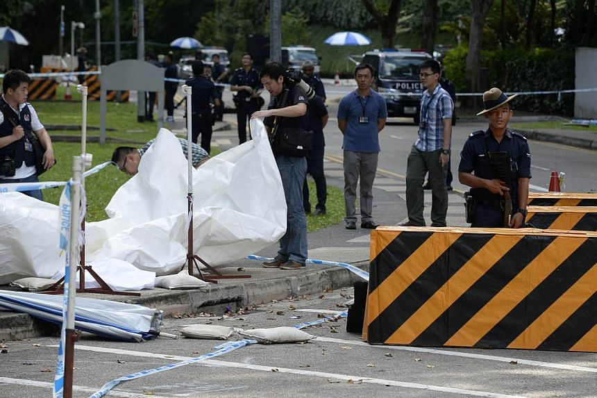 Members of the Singapore Police Force inspecting the site of a shooting at the junction of Orange Grove Road and Anderson Road, where a man was shot dead and two others were arrested after a car illegally bypassed a police vehicular checkpoint, early